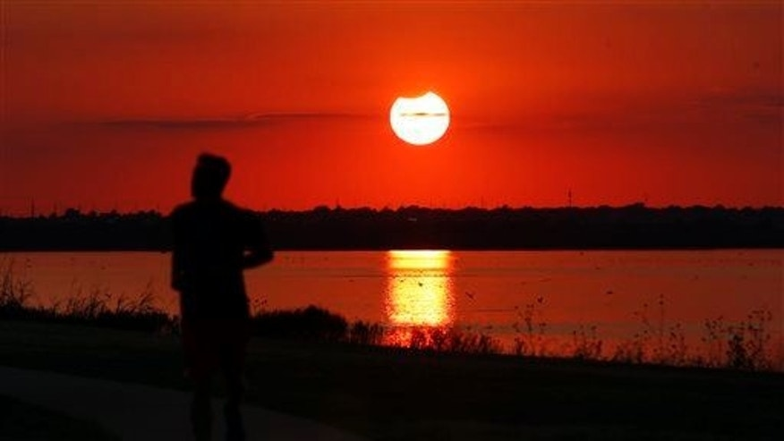 A jogger runs in front of the sun near the end of a partial solar eclipse at Lake Hefner in Oklahoma City, Thursday, Oct. 23, 2014.