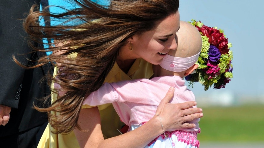 July 7, 2011: Catherine, Duchess of Cambridge, hugs 6-year-old Diamond Marshall  as she arrives in Calgary, Alberta with her husband Britain';s Prince William.