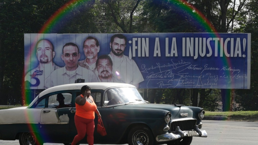 Dec. 17, 2014: A woman walks near a car in front of a banner featuring five Cuban prisoners held in U.S. custody, two of whom were previously released, in Havana.