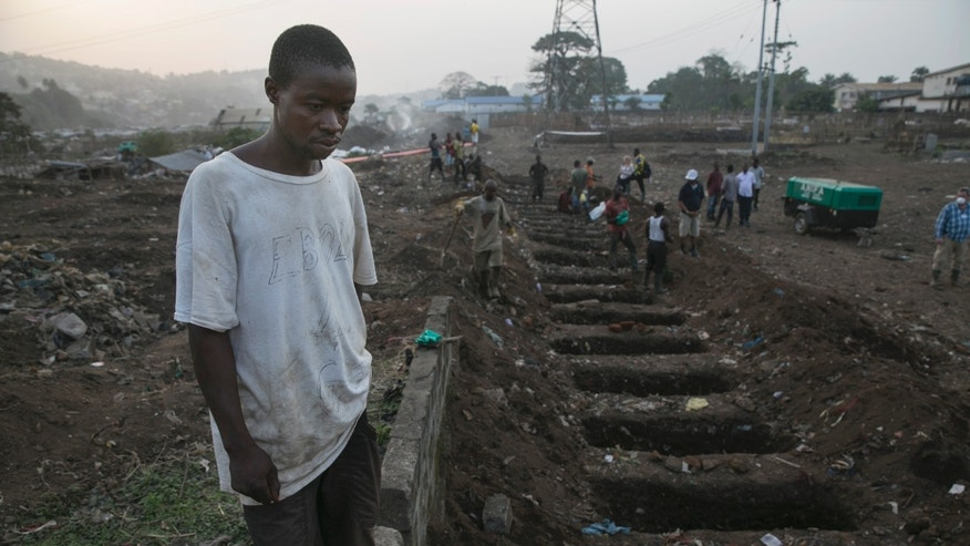 A grave digger looks at freshlydug graves for Ebola victim at a cemetery in Freetown, December 17, 2014. REUTERS/Baz Ratner