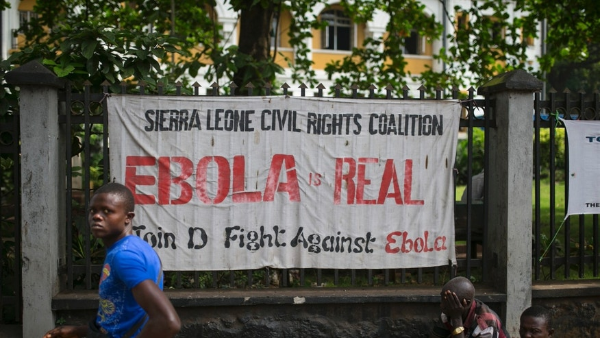 A man walks past a banner about Ebola in Freetown, Sierra Leone, December 16, 2014. REUTERS/Baz Ratner