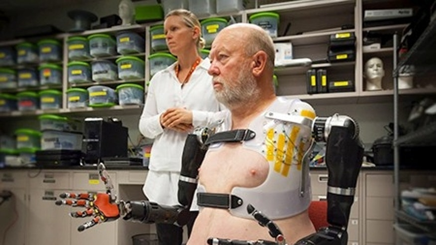 APL prosthetist Courtney Moran looks on as Les Baugh tests out the Modular Prosthetic Limbs. Image Credit: Johns Hopkins University Applied Physics Laboratory
