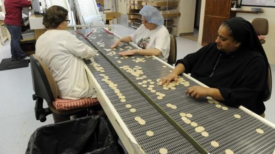 Dec. 18, 2014: Altar Bread Manager Sister Lynn Marie D'Souza (R) helps lay workers look for imperfections on some of the wheat-based communion wafers at the Benedictine Sisters of Perpetual Adoration monastery in Clyde Missouri.