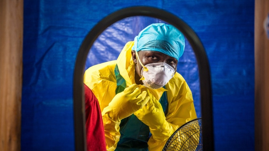 In this Thursday, Oct. 16, 2014 file photo, a healthcare worker dons protective gear before entering an Ebola treatment center in the west of Freetown, Sierra Leone. (AP Photo/Michael Duff, FILE)