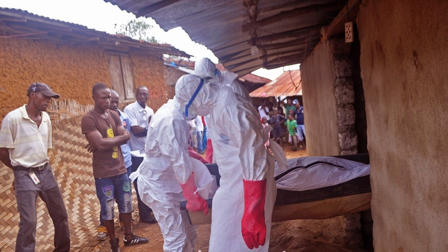 Ebola health care workers carry the body of a man suspected of dying from the Ebola virus in a small village Gbah on the outskirts of  Monrovia, Liberia, Friday, Dec. 5, 2014. (AP Photo/ Abbas Dulleh)