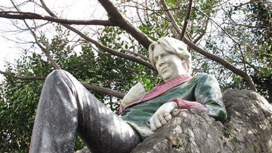 This March 14, 2014 photo shows a stone version of Oscar Wilde lounging on a rock in Merrion Square, in Dublin, Ireland.