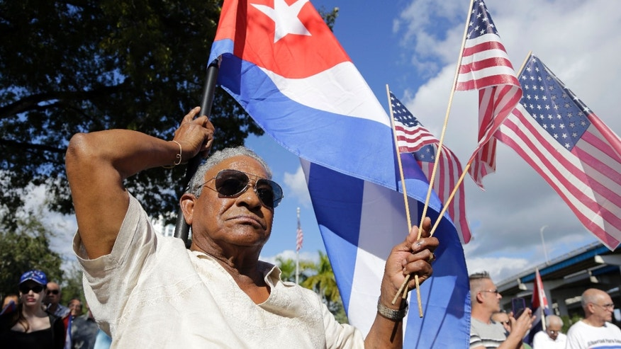 Dec. 20, 2014: Evilio Ordonez holds Cuban and American flags during a protest against President Barack Obama's plan to normalize relations with Cuba, in the Little Havana neighborhood of Miami.
