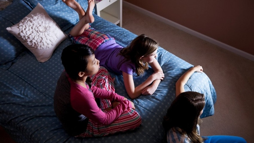 Girls sitting on bed, watching TV.