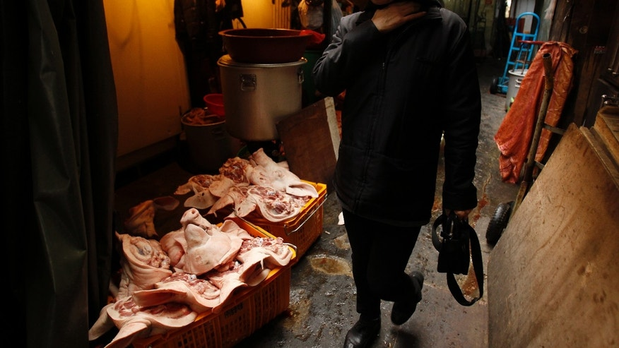 A woman walks past pig heads at a butcher in central Seoul March 18, 2011. REUTERS/Truth Leem