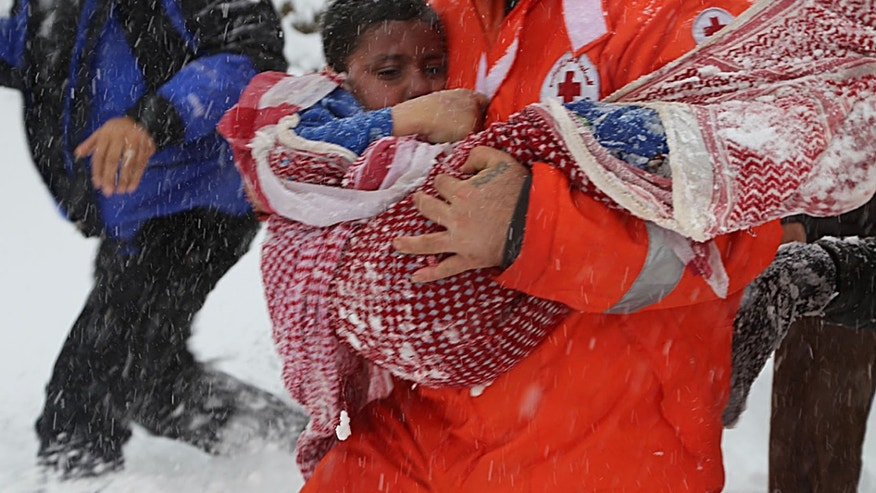 A Lebanese Red Cross volunteer carries the body of a Syrian boy, Majed Badawi, 7, who a security official said had died along with Syrian shepherd, Ammar Kamel, in a snow storm as they made the dangerous trek through the rugged, snow-covered mountains from Syria.