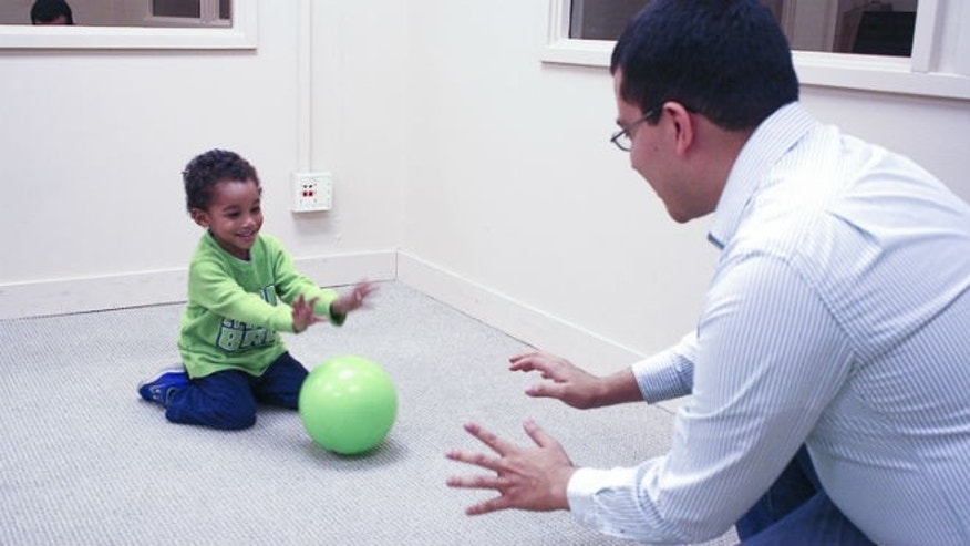 A researcher rolls a ball with a toddler, engaging in the type of reciprocal play that primes the child to exhibit future altruistic behaviors. (Stanford/Chia-wa Ye)