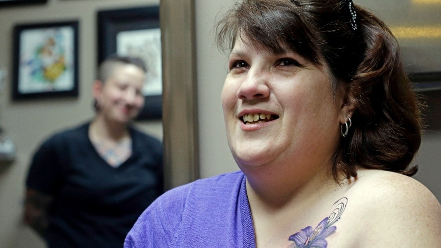 In this Wednesday, Dec. 17, 2014 photo, tattoo artist Ashley Neumann, left, watches as breast cancer survivor Mari Jankowski smiles as she talks about her new tattoo in West Allis, Wis. (AP Photo/Morry Gash)