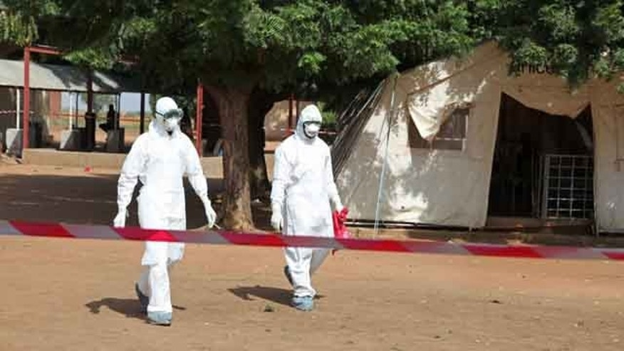 October 25, 2014: Health workers walk towards an area used for Ebola quarantine after they worked with diseased Fanta Kone at a Ebola virus center in Kayes, Mali. (AP Photo/Baba Ahmed)