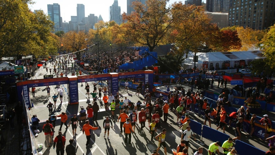 Runners cross the finish line at the end of the 2011 New York City Marathon in New York November 6, 2011.