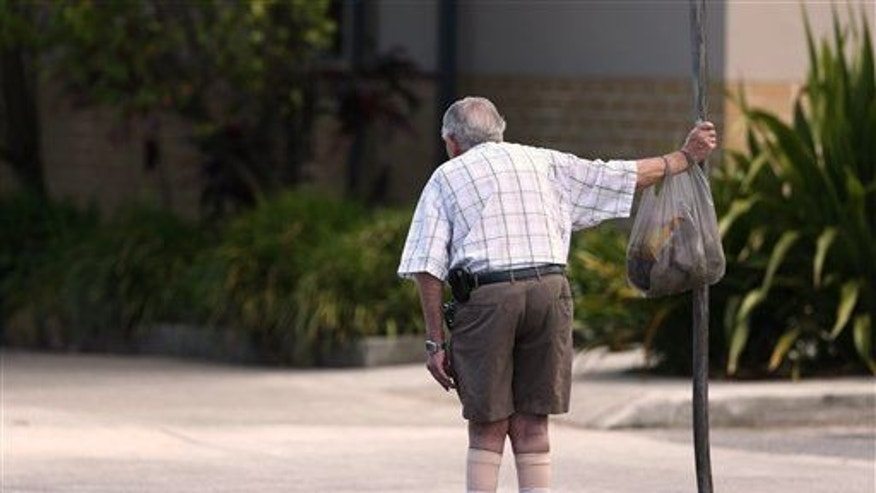 In this Oct. 11, 2013, photo, an elderly man holds onto a signpost on the side of a road in Sydney.