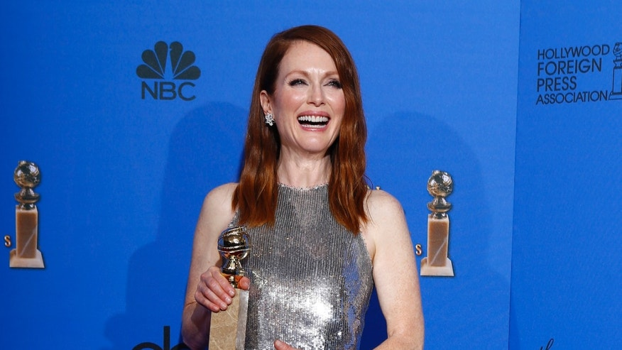"Julianne Moore poses with her award for Best Actress in a Motion Picture, Drama for her role in ""Still Alice backstage at the 72nd Golden Globe Awards in Beverly Hills, California January 11, 2015.   REUTERS/Mike Blake"