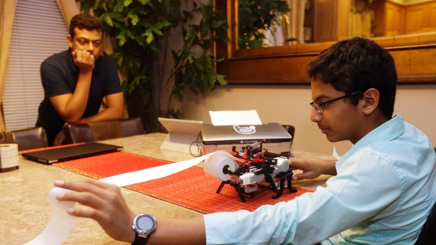 Jan. 6, 2015: Shubham Banerjee, right, world on his Lego robotics braille printer as his dad Neil watches at home in Santa Clara, Calif.