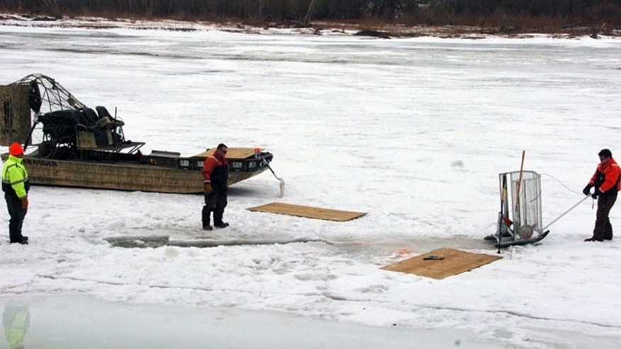 Cleanup workers cut holes into the ice on the Yellowstone River near Crane, Mont. on Monday, Jan. 19, 2015 as part of efforts to recover oil from an upstream pipeline spill that released up to 50,000 gallons of crude.