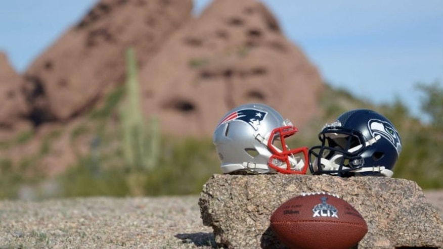 Jan 28, 2015; Tempe, AZ, USA; General view of Seattle Seahawks and New England Patriots helmets and Super XLIX logo football at Papago Park. Mandatory Credit: Kirby Lee-USA TODAY Sports