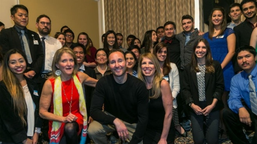 Motorcycle crash victim Brandon Levine, first row kneeling center, poses with Glendale High School students, part of the hundreds of donors of the 207 units of blood, plasma and platelets that preserved his life after a devastating motorcycle accident on April 27, 2014, that left him comatose for a month, during a ceremony at the UCLA campus in Los Angeles on Friday, Jan. 30, 2015. Next to him,at left, his mother, Betsy Sachs and his girlfriend, Leigh Horwitz. (AP Photo/Damian Dovarganes)