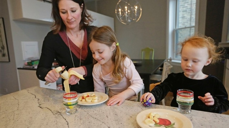 Jan. 29, 2015: Kathy Burnett prepares a snack for her daughters Claudia, center, and Sabina right, after their gymnastics class in Chicago. Burnett says she tries to feed her girls healthy, natural foods rather than commercial packaged products. (AP Photo/M. Spencer Green)