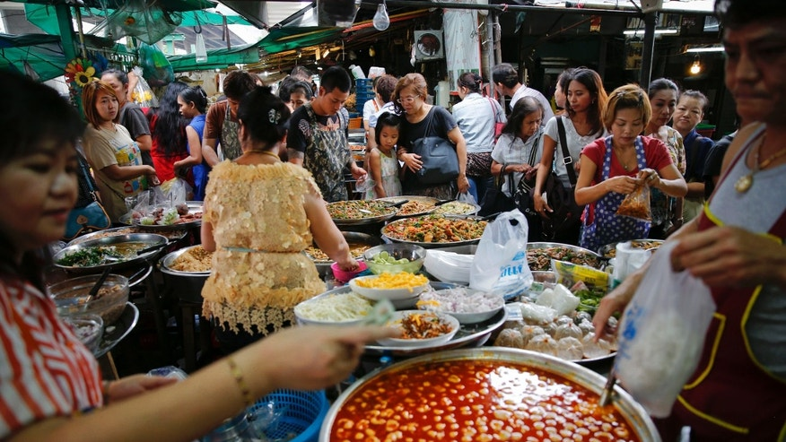 Aug. 1, 2014: People buy food at a market in central Bangkok.