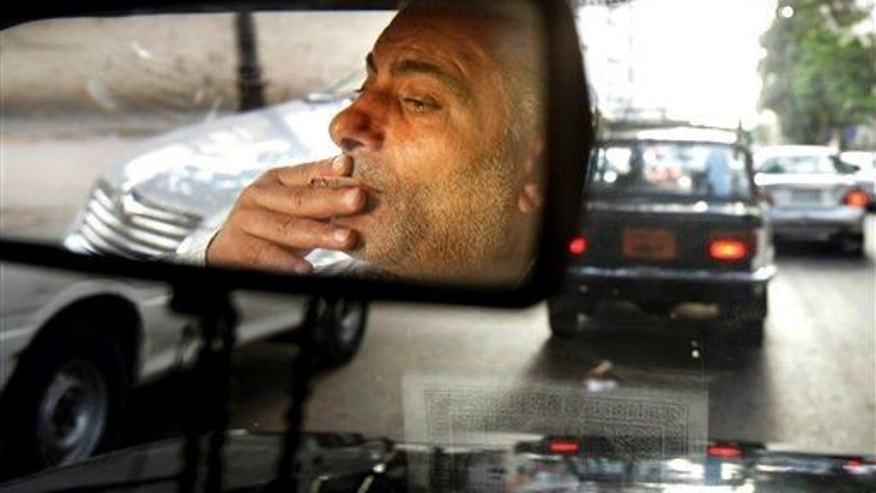 A man smokes in a car.