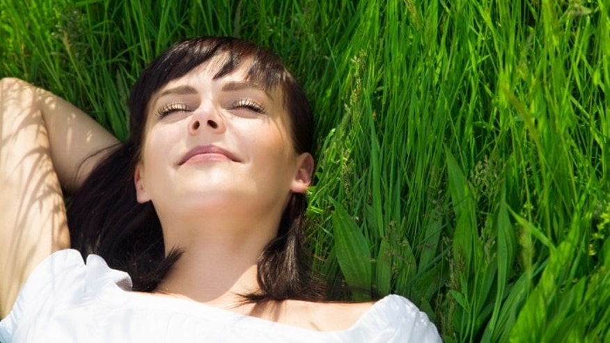 beautiful girl lying down of grass. Copy space