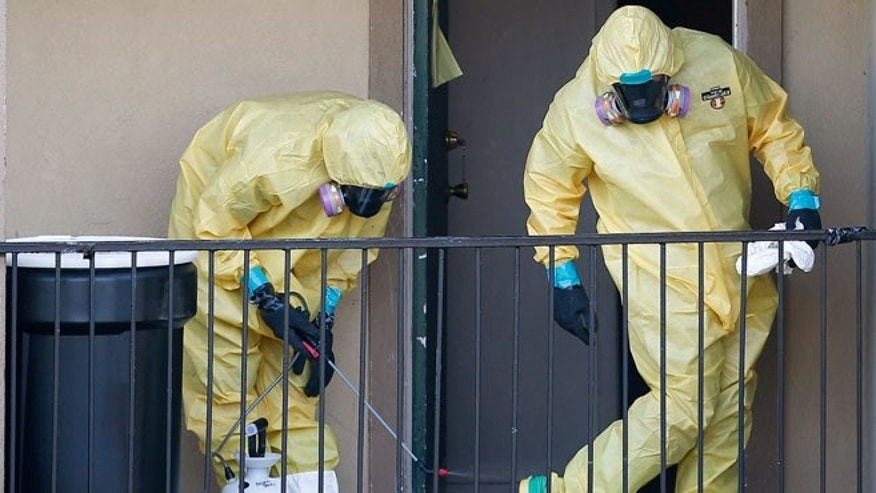 Workers in hazardous material suits clean up after removing the contents of the apartment unit where Thomas Eric Duncan, the first Ebola patient in the U.S., had been staying in Dallas, Texas, October 6, 2014.