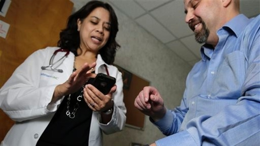 In this Thursday, Feb. 5, 2015 photograph, Hackensack University Medical Center cardiologist Dr. Sarah Timmapuri, left, looks at data on a smart phone that is synchronized to a new Fitbit Surge that is on the wrist of patient Gary Wilhelm, 51, during an examination in Hackensack, N.J.  (AP Photo/Mel Evans)