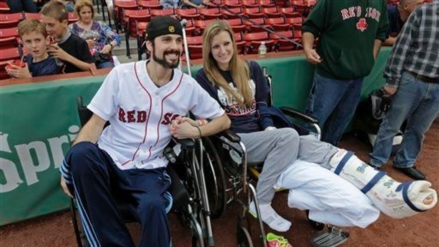 In this May 23, 2013, photo, Boston Marathon bombing survivors Pete DiMartino and Rebekah Gregory hold hands prior to DiMartino throwing out the ceremonial first pitch before a Red Sox game.