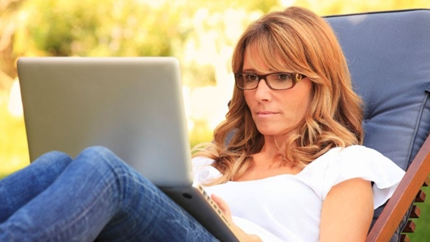 A mature woman working at home in the garden on her laptop.