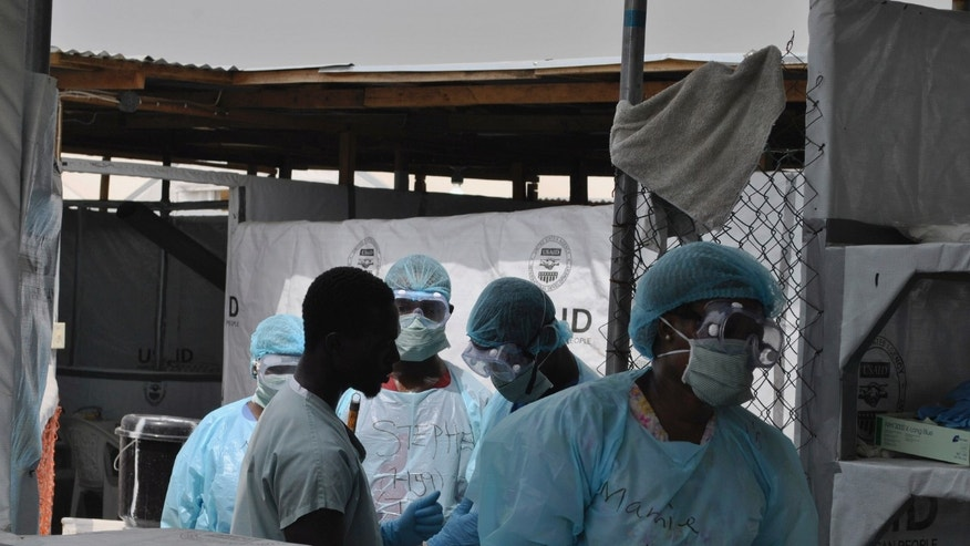 Health workers enter an Ebola treatment center in Monrovia, Liberia, December 16, 2014. REUTERS/James Giahyue
