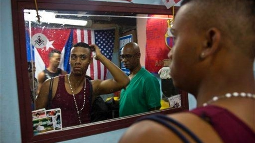 A client looks in the mirror in Havana, Feb. 27, 2015.