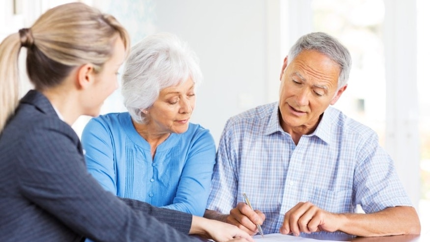 Financial advisor explaining investment plans to senior couple at home. Horizontal shot.