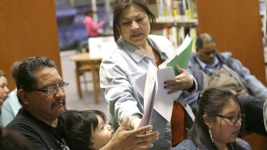 In this photo made Thursday, Feb. 12, 2015, JPS Health Network patient navigator Delaila Hernandez, center, helps Fred Cardenas with documents during a Affordable Care Act enrollment event at the Fort Worth Public Library in Fort Worth, Texas. Enrollment drives are being held across the country to help people beat the deadline to sign up for health insurance through the federal marketplace. But in Texas and more than two dozen other states where millions of people fall into a so-called coverage gap, the outreach effort has involved more than just signups.  (AP Photo/LM Otero)