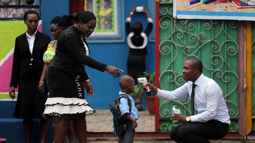 A school official takes a pupil's temperature using an infrared digital laser thermometer in front of the school premises, at the resumption of private schools, in Lagos in this September 22, 2014 file photo.  REUTERS/Akintunde Akinleye