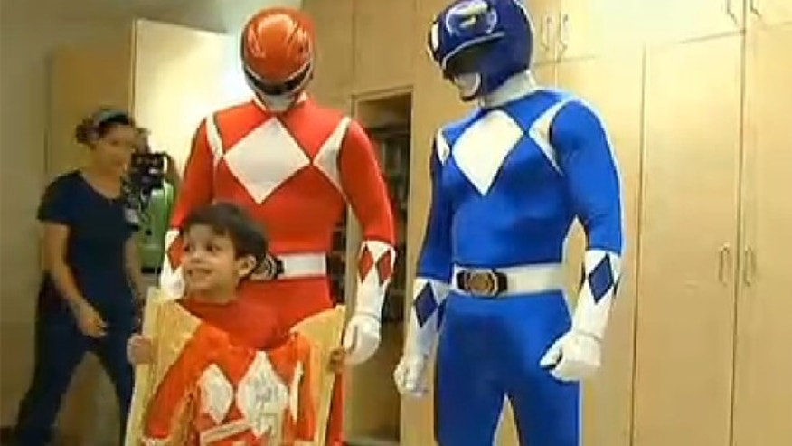 Aiden Lopez poses with his beloved Power Rangers superheroes