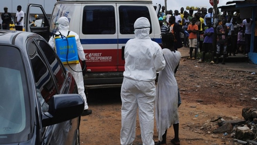 Health workers bring a woman suspected of having contracted Ebola virus to an ambulance in front of a crowd in Monrovia, Liberia, September 15, 2014. Airlines have halted many flights into and around West Africa, where governments have closed some borders and imposed travel restrictions in a bid to fight an Ebola outbreak that has killed over 2,400 people. REUTERS/James Giahyue (LIBERIA - Tags: DISASTER HEALTH) - RTR46CG3