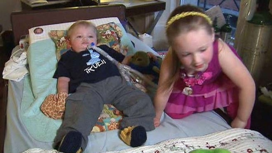 Truett Rosenlund, left, who is paralyzed from the neck down, and his 4-year-old sister.