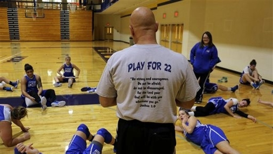 In this Oct. 23, 2014, file photo, coach Dan Benjamin wears a T-shirt with Lauren Hill's number as he runs the practice for the NCAA college basketball team at Mount St. Joseph University in Cincinnati. (AP Photo/Tom Uhlman, File)
