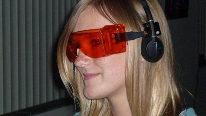 This handout photo, taken in 2009, provided by Rensselaer's Lighting Research Center, shows a subject wearing orange glasses to block blue light.