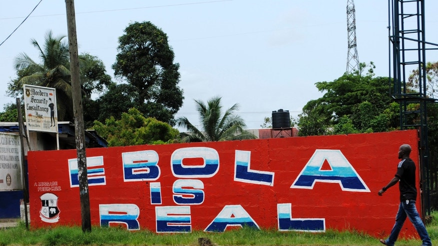"A man walks by a mural reading ""Ebola is real"" in Monrovia, Liberia, October 12, 2014. Ebola, a hemorrhagic fever, has killed more than 4,000 people since March in an epidemic centered around Liberia, Guinea and Sierra Leone. REUTERS/James Giahyue"