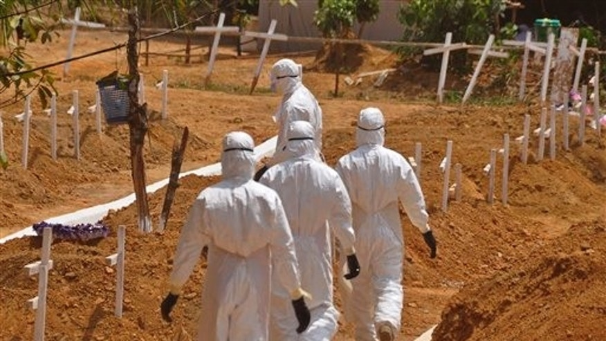 In this file photo dated Wednesday, March 11, 2015, health workers walk inside a new graveyard for Ebola victims, on the outskirts of Monrovia, Liberia. (AP Photo/Abbas Dulleh, FILE)