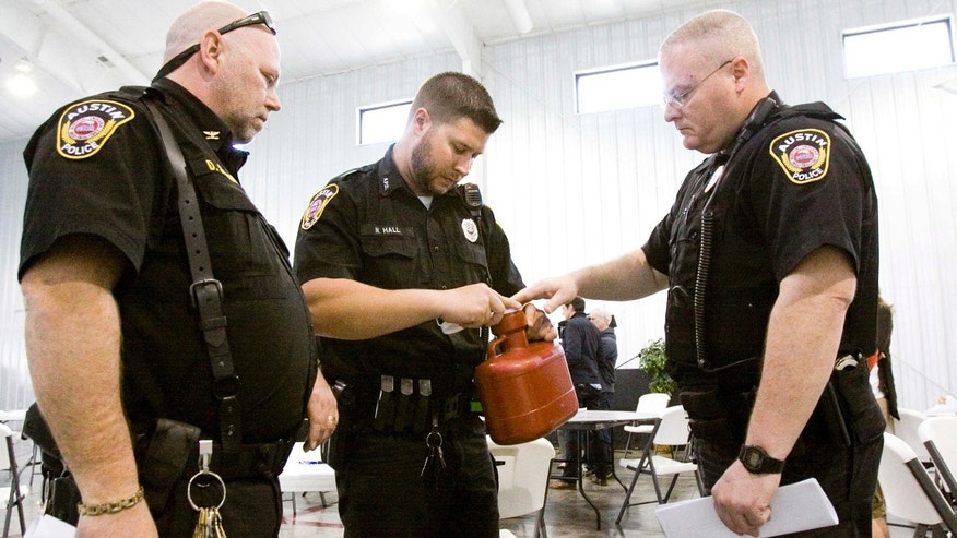 April 1, 2015: Austin Police Chief Donald Spicer, left, and Patrolman Nathan Hall, center, and Maj. Lonnie Noble study a biohazard container for the temporary disposal of needles and other sharp objects at an HIV/AIDS training session in Austin, Indiana.