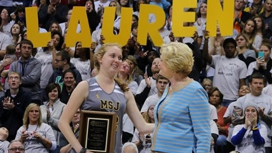 In this Nov. 2, 2014, file photo, Mount St. Joseph's Lauren Hill, left, smiles at Pat Summitt after receiving the Pat Summitt Award during halftime of her first NCAA college basketball game against Hiram University at Xavier University in Cincinnati. (AP Photo/Tom Uhlman, File)