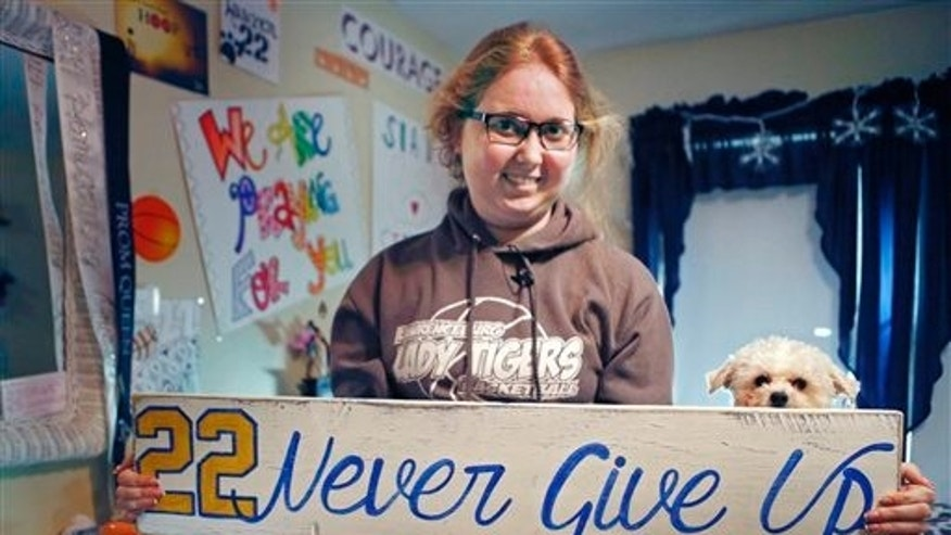 In this Dec. 8, 2014, file photo, Lauren Hill holds a sign made for her, which she keeps in her room in Cincinnati, along with many other messages and gifts of support. (AP Photo/The Enquirer, Carrie Cochran, File)
