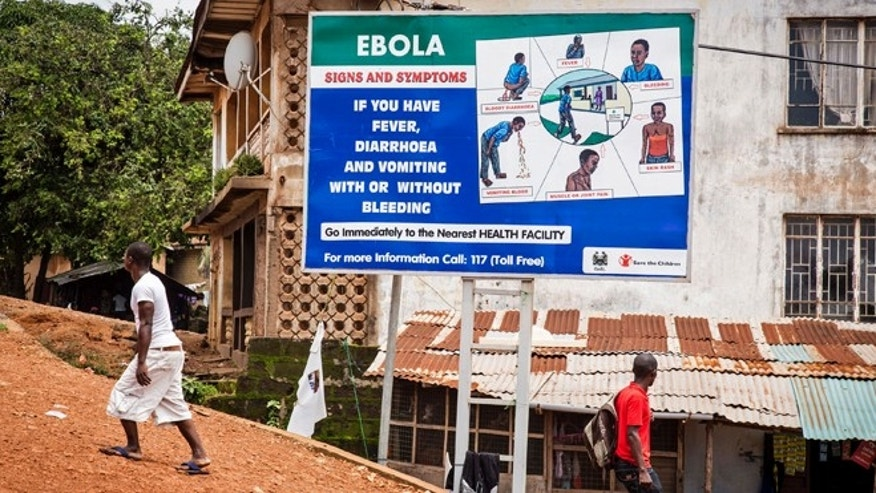 People walk past a billboard encouraging people suffering from symptoms linked to Ebola to present themselves at a health facility for treatment in Freetown, Sierra Leone, Thursday,  Aug. 7, 2014. (AP Photo/ Michael Duff)