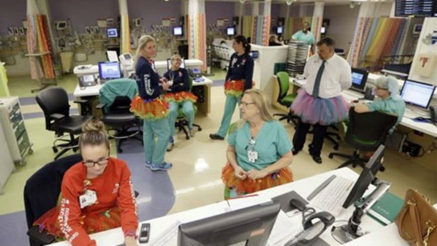 In this photo taken Tuesday, March 24, 2015, nurses and office personnel wear their tutus at the nursing station at Joe DiMaggio Children's Hospital in Hollywood, Fla., Tuesday, March 24, 2015. (AP Photo/Alan Diaz)