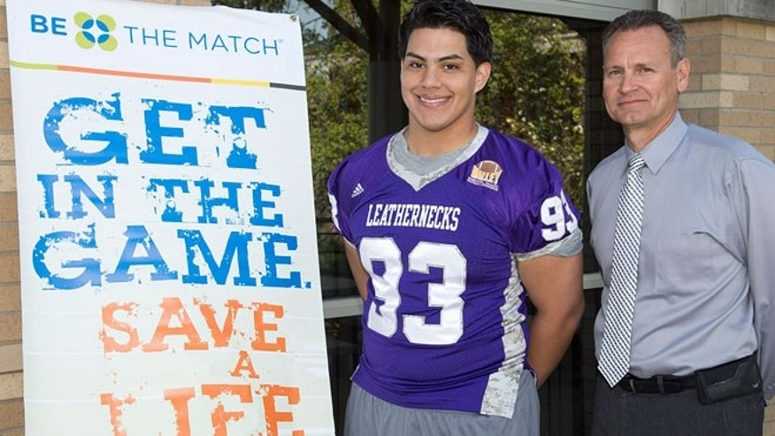 his April 23, 2015 photo provided by the Western Illinois University Visual Production Center shows 20-year-old sophomore Jordan Veloz, a linebacker for the school's football team, posing with head coach coach Bob Nielson next to a poster for the Be The Match marrow registry in Macomb, Ill. Veloz is set to become a most valuable player for an infant with a rare immune disorder. The school said Monday, April 27, 2015, that Veloz signed up last year during a bone marrow registry drive on campus. He was informed last month that he might be a match and then this month he was told that he was a match.